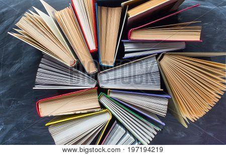 Some books on the desk over the blackboard