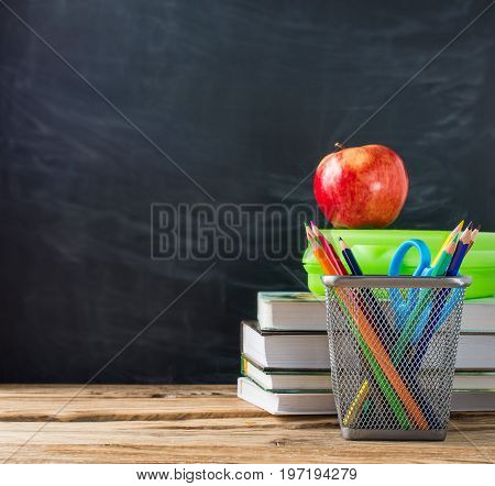 School books with stationery and apple on blackboard background