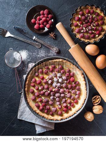 Sweet tart with raspberries and nuts powdered sugar on dark stone background.