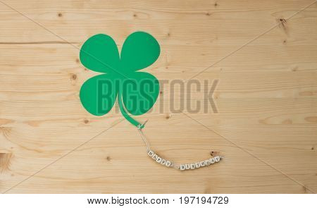 The words Happy Birthday and a cloverleaf on a cord on wood