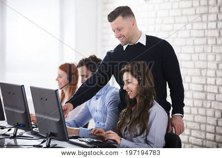 Young Businessman Showing Her Female Operator On Computer In Office