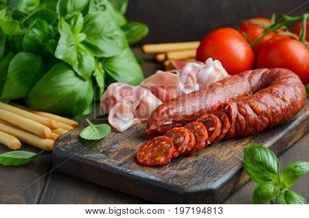 Chorizo sausage. Spanish traditional chorizo sausage and ham with fresh herbs and tomatoes.