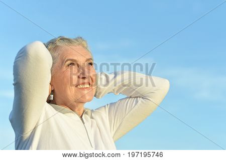 Portrait of beautiful senior woman against blue sky