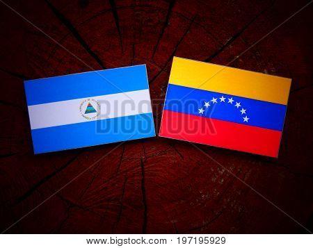 Nicaraguan Flag With Venezuelan Flag On A Tree Stump Isolated