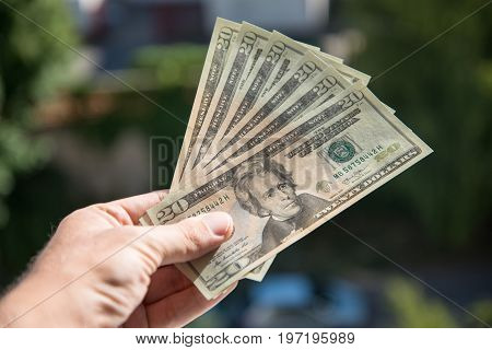 Man holding and giving couple of 20 dollar banknotes