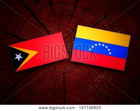 East Timorese Flag With Venezuelan Flag On A Tree Stump Isolated