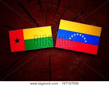Guinea Bissau Flag With Venezuelan Flag On A Tree Stump Isolated