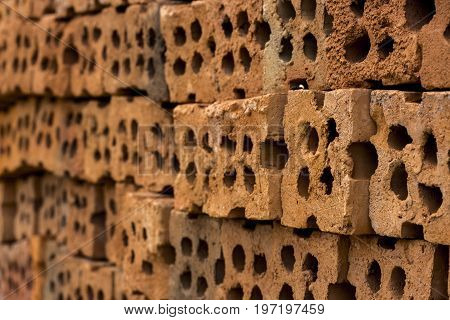 Close up of beside red clay block for wall construction. Texture of clay brick wall design with holes.