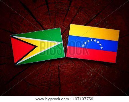 Guyana Flag With Venezuelan Flag On A Tree Stump Isolated