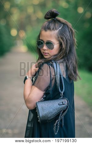 Portrait of fashionable little girl is wearing black dress and sunglasses in garden
