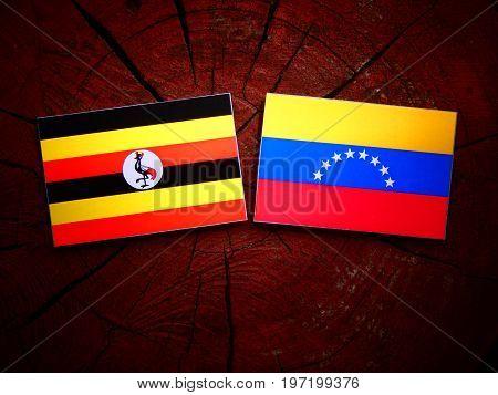 Uganda Flag With Venezuelan Flag On A Tree Stump Isolated