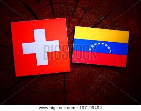 Swiss Flag With Venezuelan Flag On A Tree Stump Isolated