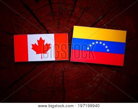 Canadian Flag With Venezuelan Flag On A Tree Stump Isolated
