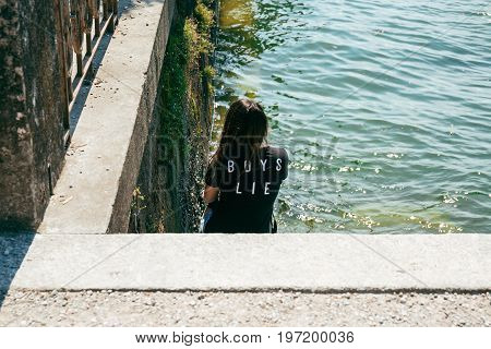 LAKE COME, ITALY - JULY 07, 2017: Young woman in a statement black t-shirt sits on steps by the lake. Lake Como is the third-largest lake in Italy.