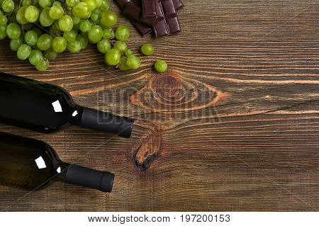 Bottles of wine and ripe grapes on wooden background. Top view. Copy space. Flat lay. Still life