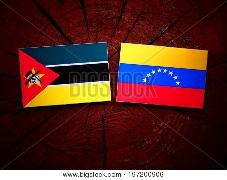 Mozambique Flag With Venezuelan Flag On A Tree Stump Isolated
