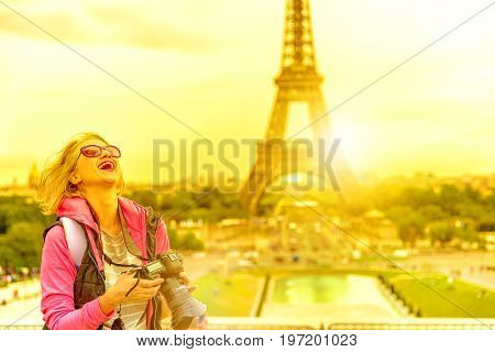 Smiling photographer with professional camera on Place du Trocadero. Traveler tourist woman in French capital, Europe. Eiffel Tower and Paris skyline on sunset background. Travel and tourism concept.