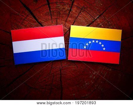 Dutch Flag With Venezuelan Flag On A Tree Stump Isolated