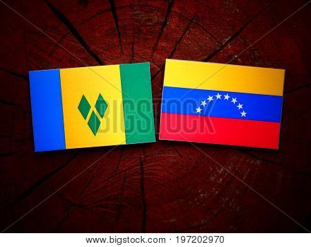 Saint Vincent And The Grenadines Flag With Venezuelan Flag On A Tree Stump Isolated