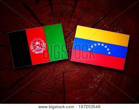 Afghani Flag With Venezuelan Flag On A Tree Stump Isolated