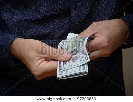 Hands counting dollar bills. Man in dark blue shirt counts the money.