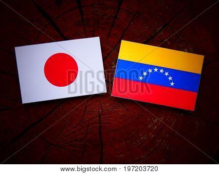 Japanese Flag With Venezuelan Flag On A Tree Stump Isolated