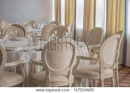 Empty tables and chairs with glasses and plates set in the restaurant