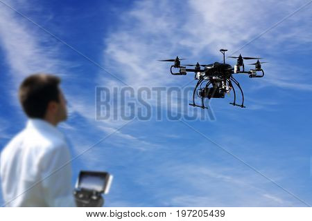 pilot is flying the drone with the camera with blue sky and clouds background