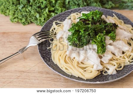 Plate with homemade pasta. Spaghetti with white bechamel sauce sliced chicken breast kale chips served with metal fork on wooden board with fresh kale leaves