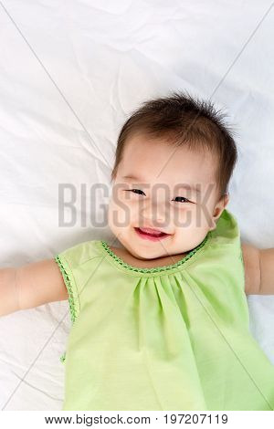 Portrait Of A Little Adorable Infant Baby Girl Lying On Back On Bed And Looking In Camera Indoors