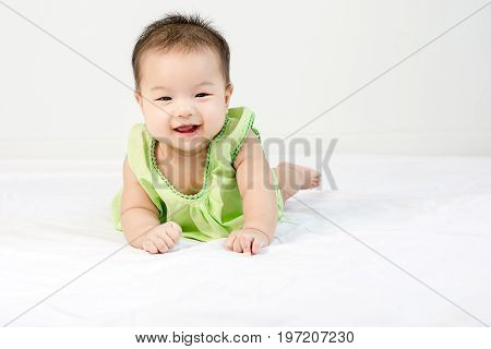 Portrait Of A Little Adorable Infant Baby Girl With Saliva Lying On The Tummy On Bed And Looking In