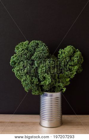 Vertical background with raw kale in a metal jar. Fresh kale leaves