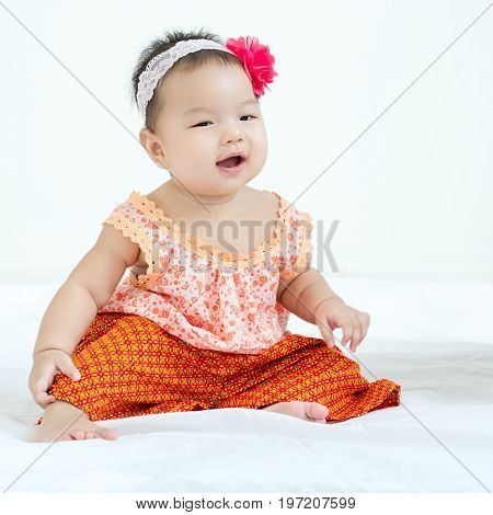 Portrait Of A Little Adorable Infant Baby Girl Sitting On The Bed And Smiling To The Right Side With