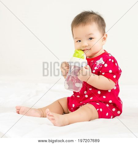 Portrait Of A Little Adorable Infant Baby Girl Drinking Water In The Bottle And Looking To Camera In