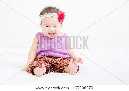 Portrait Of A Little Adorable Infant Baby Girl Sitting On The Bed And Smiling To Camera With Copyspa