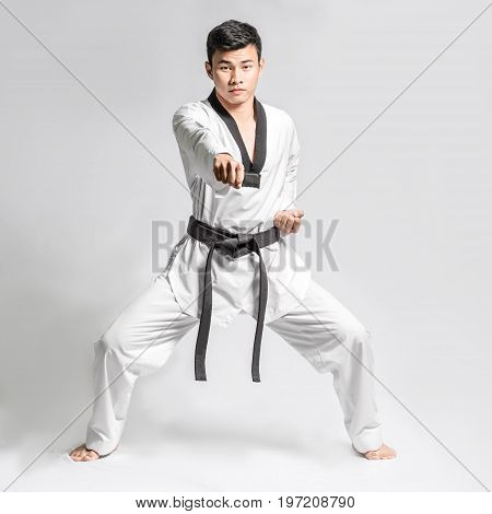 Portrait Of An Asian Professional Taekwondo Black Belt Degree (dan) Preparing For Fight. Isolated Fu