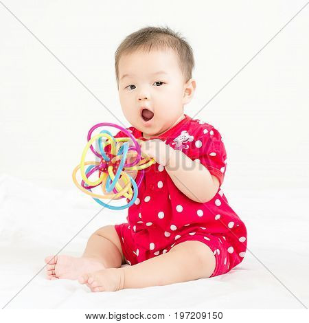 Portrait Of A Little Adorable Infant Baby Girl Sitting On The Bed And Smiling To Camera With Bites T