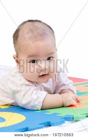 Portrait Of A Little Adorable Newborn Infant Baby Girl With Saliva Lying On The Tummy On Colorful Ev