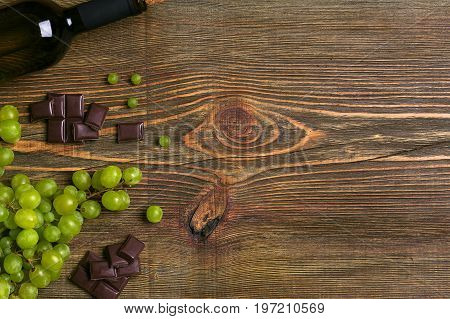 Bottle of wine and ripe grapes on wooden background. Top view. Copy space. Flat lay. Still life
