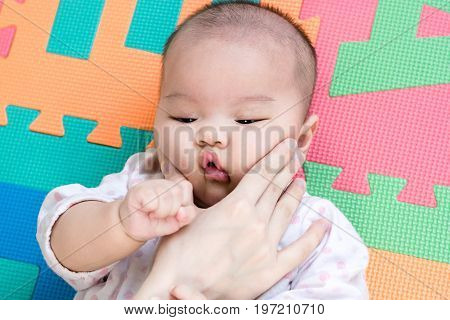 Parent Pinch The Cheeks A Little Adorable Newborn Infant Baby Girl That Lying On The Back On Colorfu