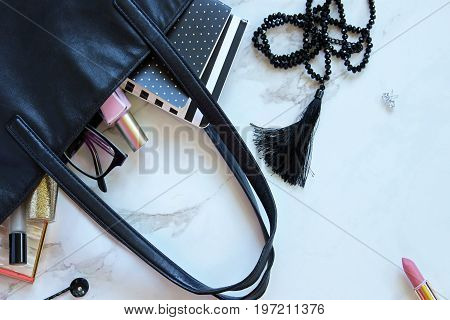 Black leather tote spilling with pink and black fashion and beauty supplies. White copy space.