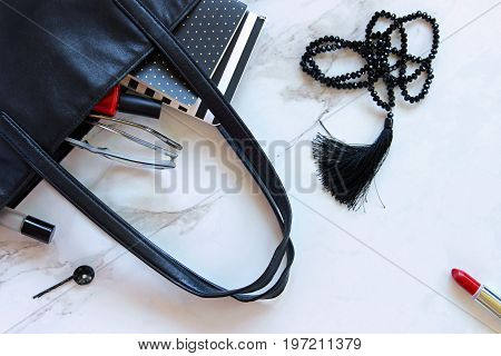 Black leather tote bag spilling with red and black fashion and beauty items. Copy space.