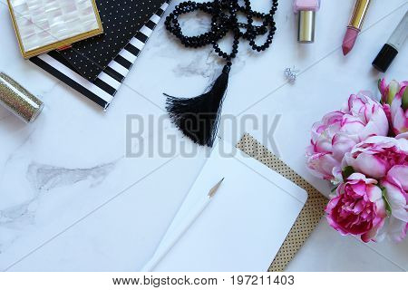 Black, white and pink beauty and fashion supplies frame white copy space with flowers and blank note card.