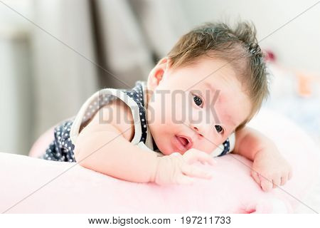 Portrait Of A Little Adorable Infant Baby Girl Lying On The Tummy On The Pillow And Looking In Camer