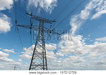 high voltage pylons on blue cloudy sky background