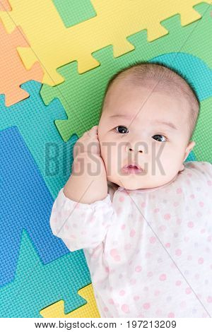 Portrait Of A Little Adorable Infant Baby Girl Lying On Back On Colorful Eva Foam And Looking In Cam