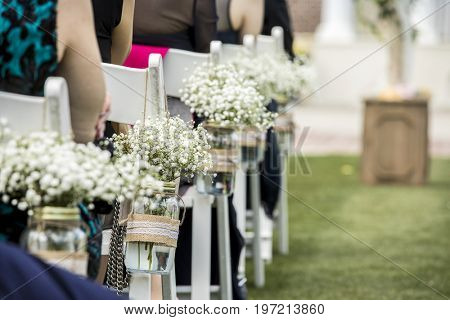 Chairs, hanging jars with flowers, and guests at wedding.