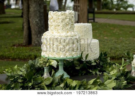 Pair of two tiered wedding cakes at outdoor wedding reception
