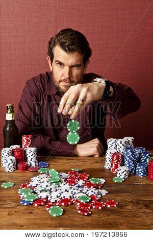 Man dropping poker chips to make bet during poker game, studio shot