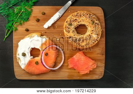 A photo of a bagel with cream cheese and lox, with a purple onion, a sprig of dill, and capers, shot from above on a black texture with a place for text